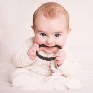 bébé qui se soulage les dents avec anneau de dentition